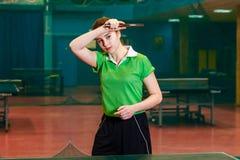 Caucasoid schönes brunette Mädchen, das Tischtennis in einer Turnhalle spielt lizenzfreie stockfotografie