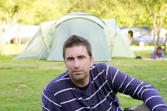Caucassian man relaxed on camping meadow. Caucassian man relaxed on the tent camping meadow Royalty Free Stock Photography