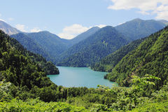 Caucasus. Abkhazia. Riza lake with clear blue water, surrounded by lush green forest. Against the blue sky with clouds, a sunny summer day Stock Photos