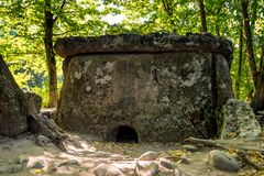 Caucasus dolmen in forest. Ancient portal dolmen standing in scenic forest Stock Image