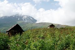 Caucasus mountain scenery. Mountain scenery in Upper Svaneti region in Georgia. Huts serve as a temporary living place for herdsmen during summer Royalty Free Stock Photo