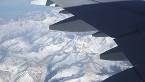 The Caucasus mountains beneath the wing of airliner, aerial view. From high altitude clip stock video footage