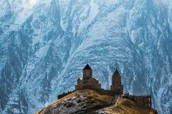 Caucasus mountains, Gergeti Trinity church, Georgia. Caucasus mountains, ancient Gergeti Trinity church Tsminda Sameba against the glacier near mount Kazbek Stock Photo