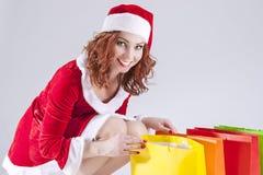 Caucásico sonriente feliz Ginger Santa Helper Girl con los panieres coloridos Imágenes de archivo libres de regalías