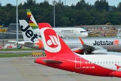 Caudas de Air Zimbabwe Boeing 767, de Jetstar Ásia Airbus A320 e de ar Belin Airbus A320 no aeroporto de Changi Imagem de Stock
