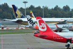 Caudas de aviões de Singapore Airlines, de Air Zimbabwe, de Jetstar Ásia e de Air Berlin no aeroporto de Changi Foto de Stock