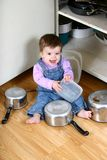 Caught in the Act. Adorable baby girl pulling pots and pans and other dishes out of a kitchen cupboard stock photo