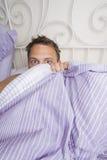 Caught in the Act. Man hiding under the duvet Stock Photos