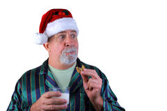 Caught in the Act. Grandpa Santa Claus is caught in the act of eating the cookies and drinking the milk left by the kids on Christmas Eve Royalty Free Stock Photos