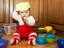 Caught in the Act. Adorable baby girl pulling pots and pans and other dishes out of a kitchen cupboard Stock Photos