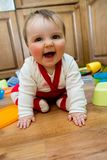 Caught in the Act. Adorable baby girl pulling pots and pans and other dishes out of a kitchen cupboard Royalty Free Stock Image