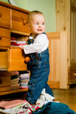 Caught in the act. Baby throws out clothes from wooden furniture at home Royalty Free Stock Photos