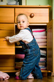 Caught in the act. Baby throws out clothes from wooden furniture at home Royalty Free Stock Photography