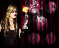 Caught in the act of setting the stage on fire. Beautiful blonde hoodlum captured in arson act holding burning petrol bomb intent on setting the theatre on fire Royalty Free Stock Images
