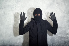 Caught burglar. Catch the burglar concept, thief with balaclava caught in front of the grunge concrete wall stock photo