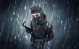Caught burglar by house camera in action. Burglar in action in black clothes with rainy concept Royalty Free Stock Photography