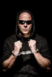 Caught criminal. Criminal with sunglasses and hood trapped in handcuffs Stock Photo