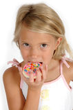 Caught eating a cookie!. A child takes a bite of a cookie coated in icing and sprinkles. Can be used for dentists and cavities. Teaching children about healthier Stock Image