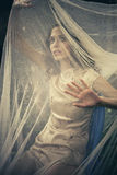 Caught in the net. Woman trying to find a way out of net  outdoor shot Stock Photography