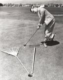Caught between a rake and a gardening fork on the putting green Royalty Free Stock Photo