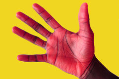 Caught Red Handed- Blackhand 2. This is an image of a black hand that has been 'hued ' to appear red. Gold background royalty free stock photo
