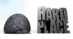 Caught Between A Rock And A Hard Place. A literal description of the saying a rock and a hard place with a big black rock and a metal hard place with a space Stock Photo