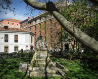 Caught by Shadows. Statue covered by trees` shadows at the front of old buildings in Madrid, Spain Stock Photo