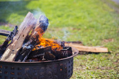 Cauldran Fire on Grass Field. Campfire logs burning in a cauldron that is off-center Stock Photo