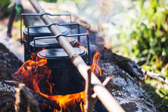 Cauldron boils on the fire, camping in the forest. In marching a Stock Photography