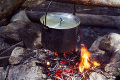 Cauldron boils on the fire in the forest. In marching a saucepan preparing food. Adventure tourism, camping, cooking on a fire. Survival in the forest. Stalker stock image