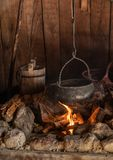 Cauldron cooking over an open fire in the cabin stock photography