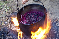 Cauldron with jam of the forest berries. Jam boiling on the fire in the cauldron Royalty Free Stock Image