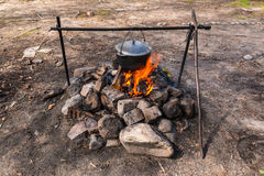 Cauldron over campfire. Cauldron hanging over the burning fire Stock Image