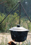 Pot for cooking on a fire in a campaign. Cauldron with soup over a fire on the lake Royalty Free Stock Photography
