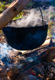 Cauldron in steam and smoke on open fire. Outdoor cooking concept. old fashioned way to make food Royalty Free Stock Photography