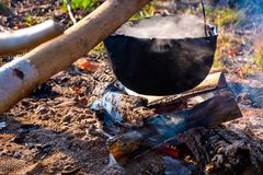 Cauldron in steam and smoke on open fire. Outdoor cooking concept. old fashioned way to make food Royalty Free Stock Images
