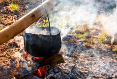 Cauldron in steam and smoke on open fire. Outdoor cooking concept. old fashioned way to make food Stock Images