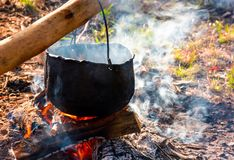 Cauldron in steam and smoke on open fire. Outdoor cooking concept. old fashioned way to make food Royalty Free Stock Photo