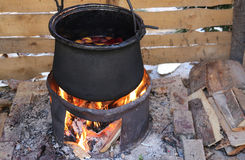 Cauldron to cook the tasty mulled wine in the country festival Stock Image