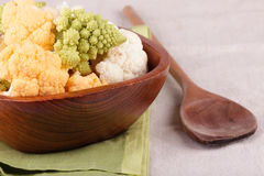 Cauliflower in the bowl. Different colours cauliflower in the bowl on green tea-towel Royalty Free Stock Images