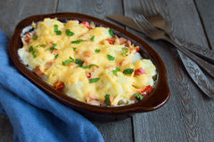 Cauliflower and cheese gratin. In baking dish on rustic wooden background stock photos