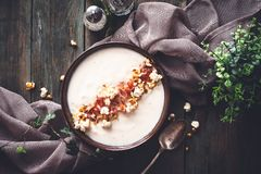 Cauliflower Creamy Soup with Curry Popcorn and Speck Ham. On wooden background royalty free stock image