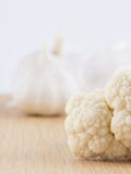 Cauliflower floret and head of garlic. On wooden chopping board Stock Photography