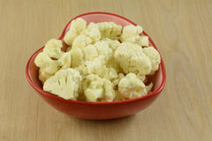 Cauliflower florets. Heart healthy cauliflower florets in red heart shaped bowl Royalty Free Stock Images