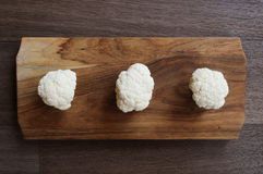 Cauliflower florets on wooden board. Indoor photography of cauliflower Stock Photo