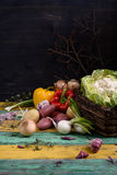 Cauliflower with fresh raw vegetables, healthy cooking ingredients on rustic wooden table. Vegetarian diet background. Stock Photo