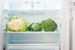 Cauliflower, green cabbage and green broccoli on shelf of open empty refrigerator. Weight loss diet concept Stock Photography