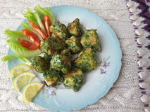 Cauliflower in green nettles tempura, fritters cooking vegetarian food with nettles. Lemon and tomato royalty free stock image