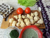 Cauliflower in green nettles tempura, fritters cooking vegetarian food with nettles. Lemon and tomato stock photography