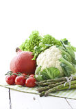 Cauliflower, pumpkin, tomato and asparagus. Fresh vegetables and greens on white wooden table royalty free stock photos